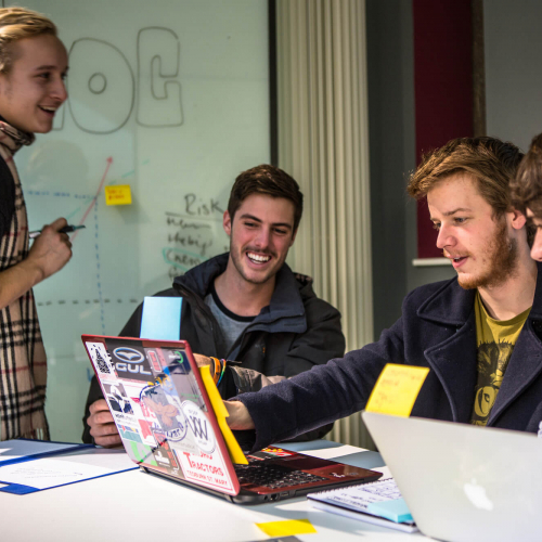 Falmouth University Business students smiling and looking at a laptop