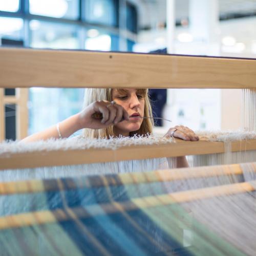 Student working on loom.
