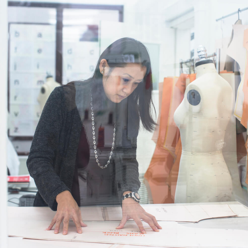 A Costume Design student at a mannequin with pattern cuttings hanging up