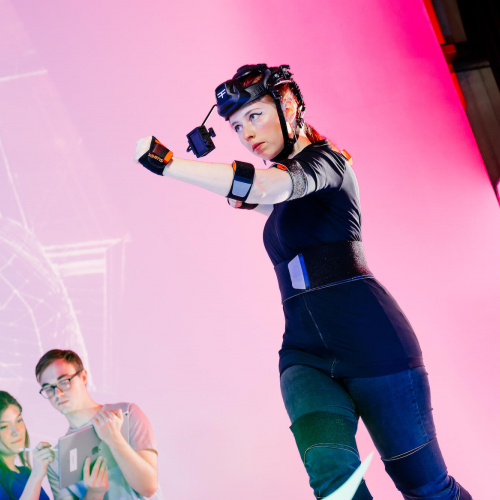 Female student wearing games development headset in front of a pink background