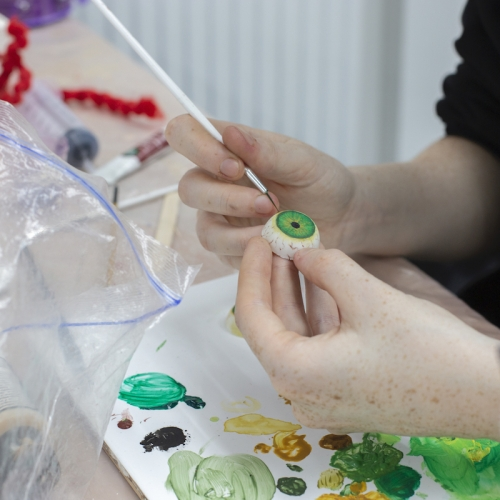 A student painting a 3D eye with green paint