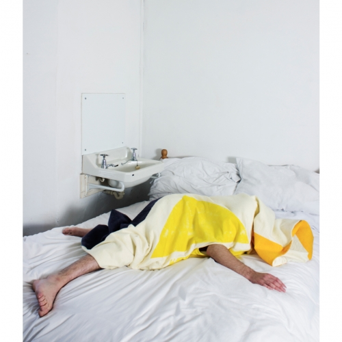 Model lying face down on bed in yellow triangle printed outfit covering head.