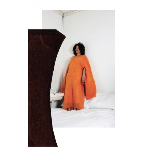 Model stood on bed in long orange dress with billowing sleeves.