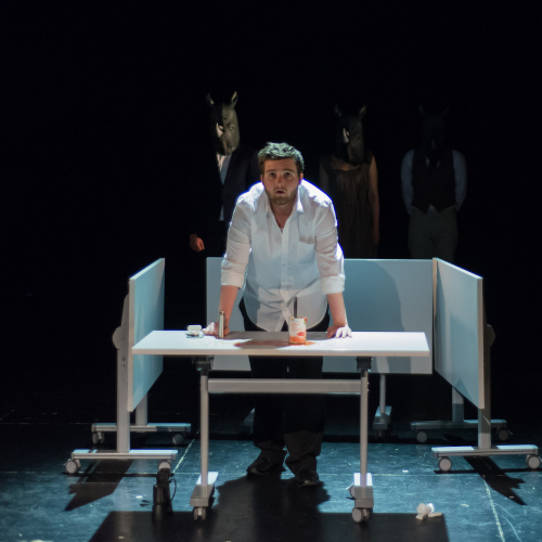 Falmouth University actor in a white shirt, leaning on a desk