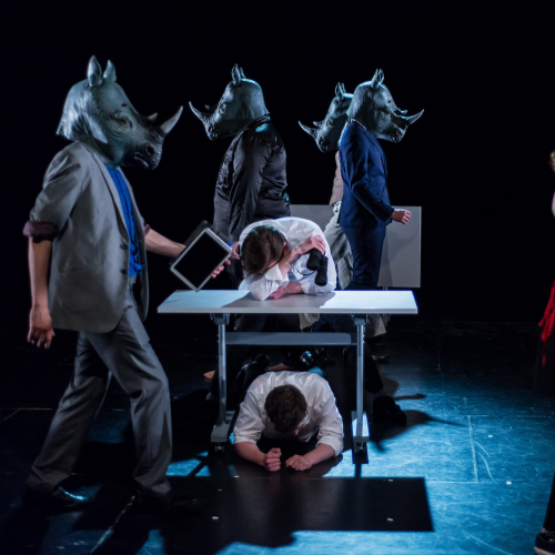 Actors with Rhinoceros masks on stage at AMATA