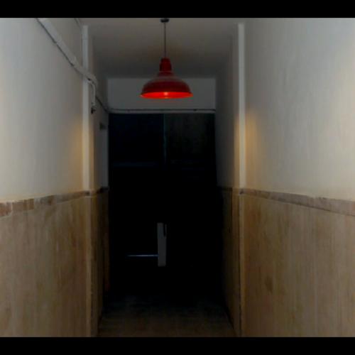 Red ceiling light hanging in narrow corridor.
