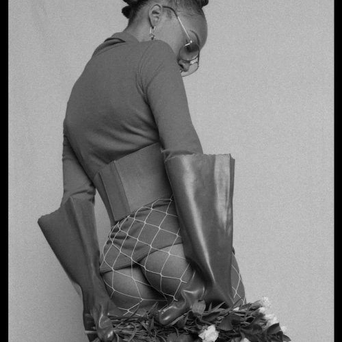 Model wearing white fishnets, rubber gloves, holding flowers.
