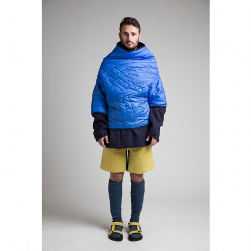 Model in knee length socks and sandals and padded blue sweater with funnel neck.