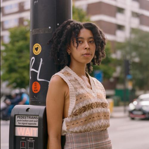 Woman poses by sidewalk