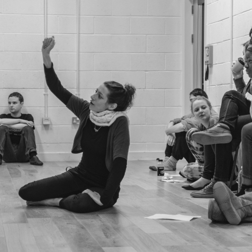 Falmouth University Acting student sitting down with her arm raised above head