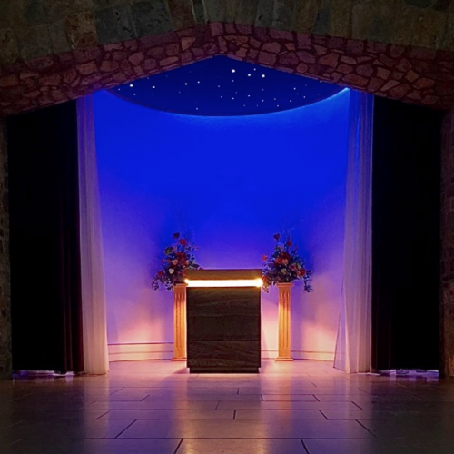 A stage lit in blue light with columns and flowers