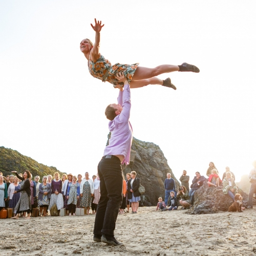 man raising a woman above his head on a beach surrounded by a crowd