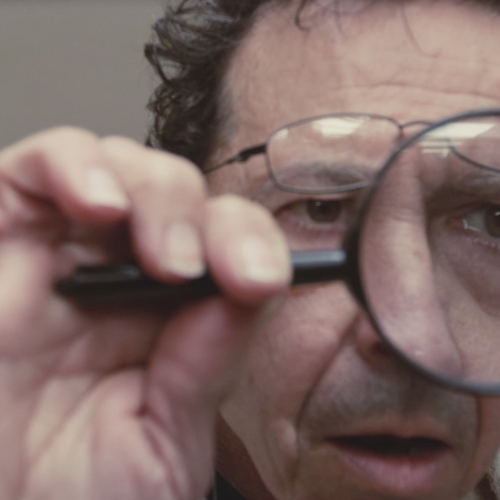 Film still, close up of a male face looking through a magnifying glass.