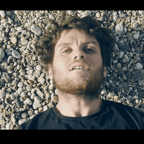 Shoulders and head shot of actor with beard lying on a beach.