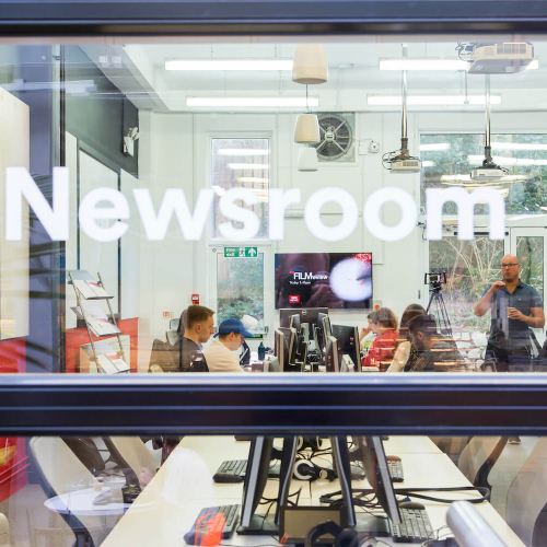 Through the window of the newsroom with lecturer talking to journalism students.