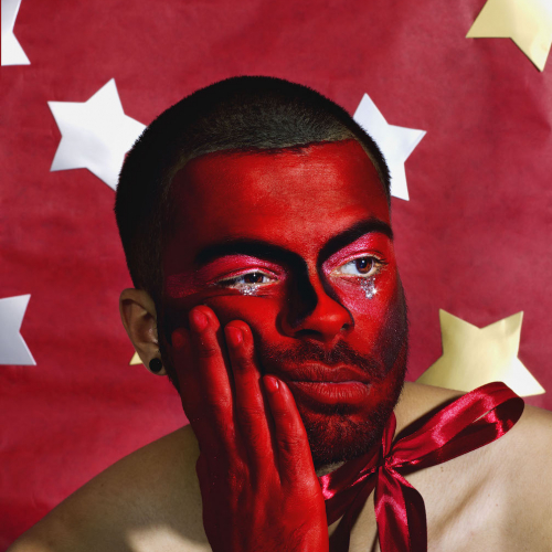 Man painted with red and tears of sparkles in front of red backdrop with stars.