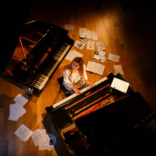 Girl sat in between two pianos, sheet music scattered over the floor.