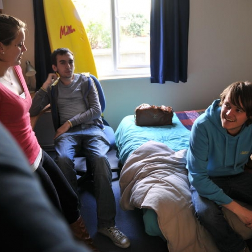 Students sitting around a bedroom and chatting.