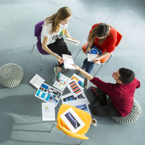 Falmouth University Business students sat on chairs on grey floor looking at work together.