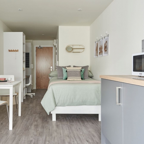 Studio apartment with bed, dining table and kitchen top