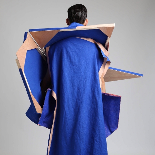 A person dressed in a blue robe with pointed angles