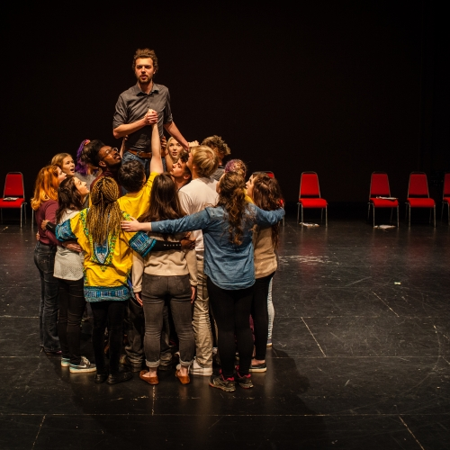 Group of student actors hugging in a circle with one actor raised up in the middle.