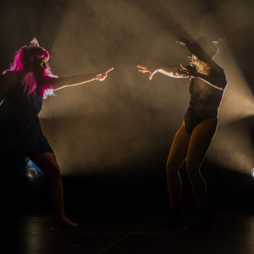 Actors dancing in a smoky and dim light on the stage.