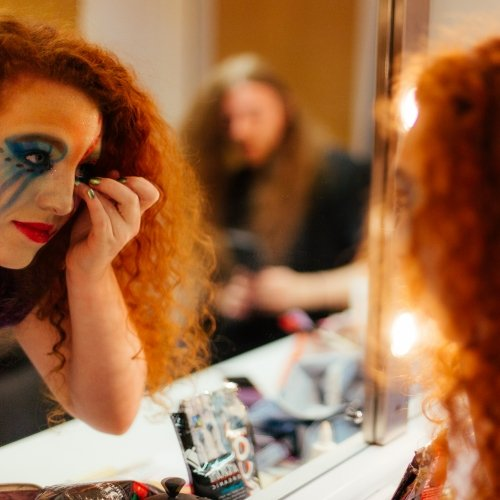 Student actor with dramatic make up looking in mirror in dressing room and touching her face.