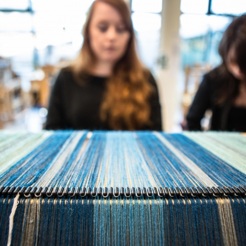 Textile students working on a loom.