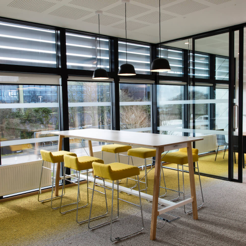 Yellow stools inside the Creative Bridge building on Penryn Campus