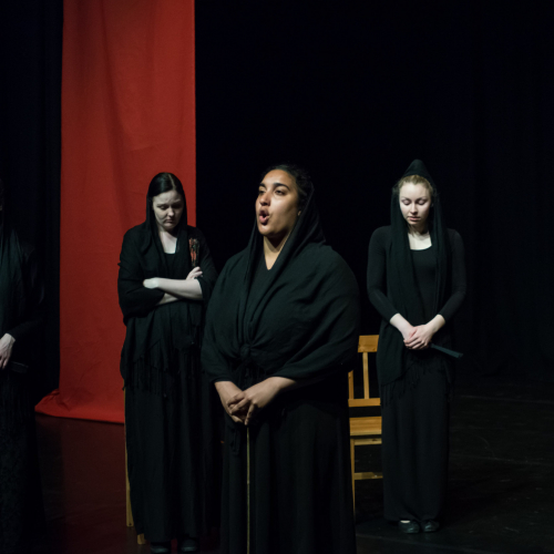 An Acting student dressed in black, speaking, with other actings looking at the floor