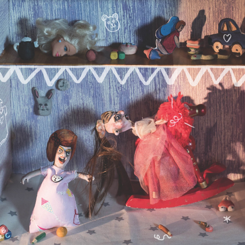 Two women puppets fighting with one pulling hair of the other on a red rocking horse.
