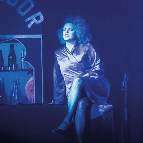 Actor in satin dressing gown singing and lit in blue light.