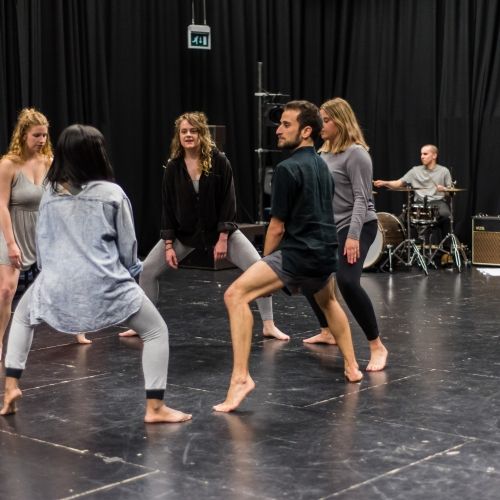 Group of students rehearsing in a circle on tiptoes with knees bent.