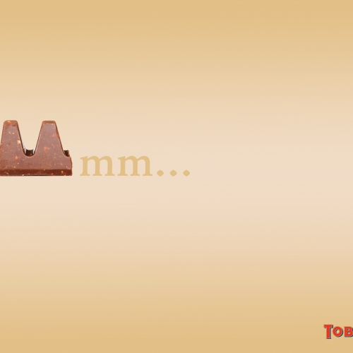 "Advert for Toblerone with 2 triangles making the first ""m"" of the word mmm."