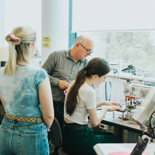 Students and teacher in textiles studio with one student at a sewing machine