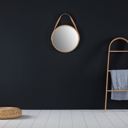 A circle mirror and curved towel rail made from steam bent wood by the designer, Tom Raffield.