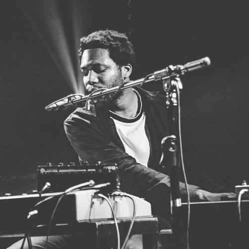A male student singing into a microphone while seated and playing the piano