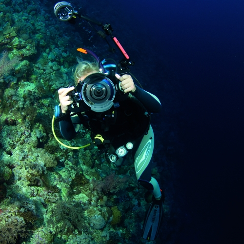 Student underwater pointing camera at the photographer.