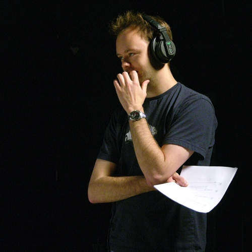 Male holding paper and wearing headphones.