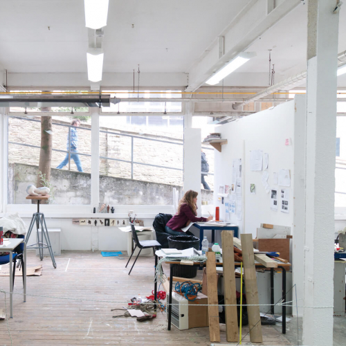 Art student working in studio with large window on Falmouth campus and person walking past and looking in.