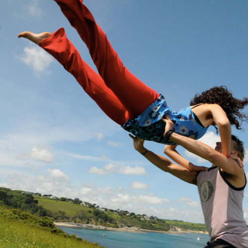 A male dancer lifting a female dancer high in the air on grass with the sea and sky in the background
