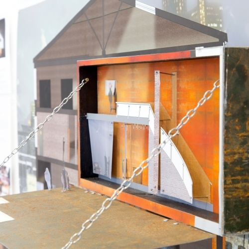 Cardboard mock up of interior with orange wall and front wall folded down and held with chains.
