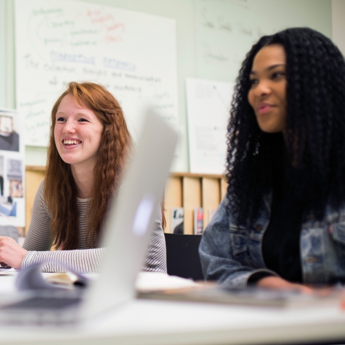 Smiling fashion marketing students working together around a desk.