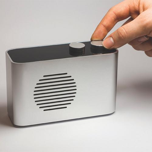 A hand tuning a silver radio