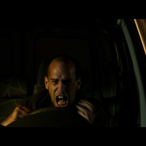 A man screaming at the car wheel with a town lit up at night in the background