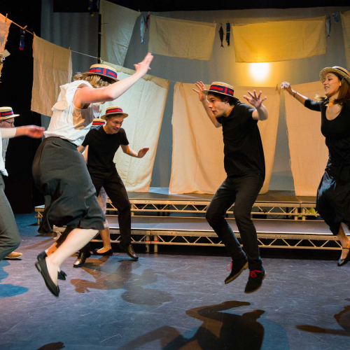 Falmouth University student actors wearing boater hats and jumping on stage