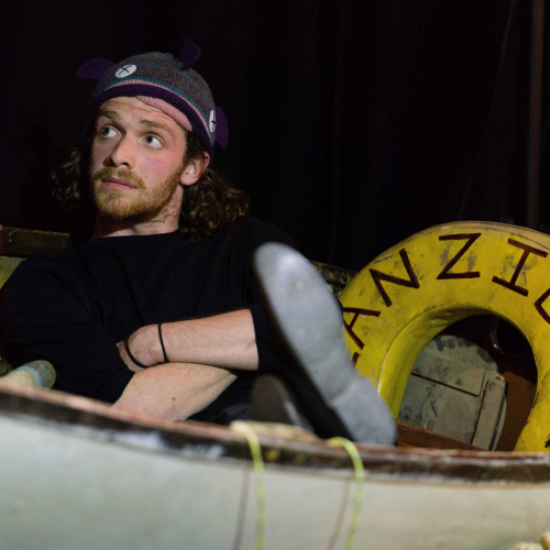 Student acting as a fisherman sitting in a boat