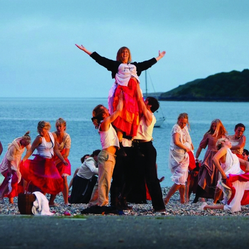 Dancers dressed in red and white performing on beach.
