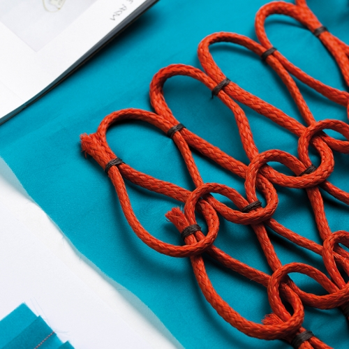 Red cord woven in pattern on a turquoise blue fabric.